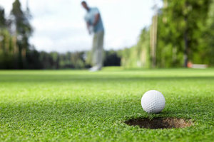 Closeup of a golfer making a putt into a hole